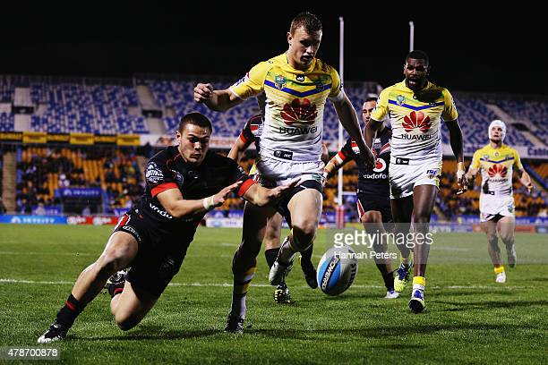 Jack Wighton of the Raiders looks on as Tuimoala Lolohea of the Warriors scores a try around him during the round 16 NRL match between the New...