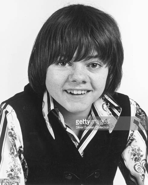 Jack Wild British actor wearing a black tank top over a print pattern shirt in a studio portrait against a white background circa 1965