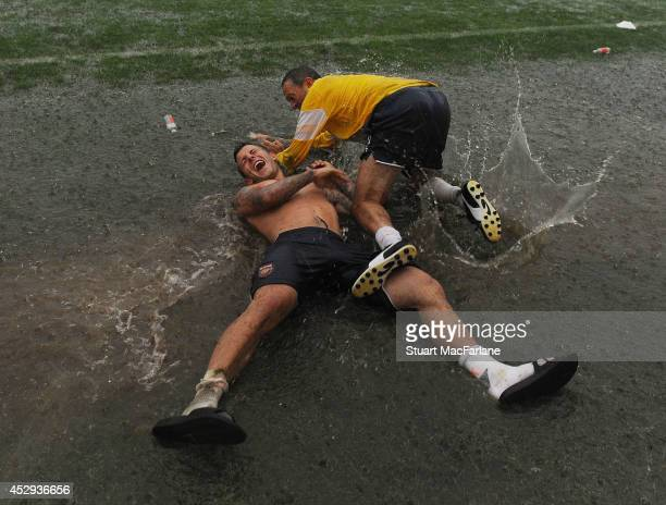 Jack Wilshere and Arsenal equipment manager Paul Johnson enjoying the wet conditions after a training session on July 30 2014 in Bad Waltersdorf...