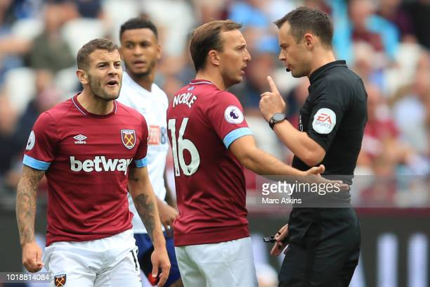 Jack Wilshere and Mark Noble of West Ham United argue with Referee Stuart Attwell during the Premier League match between West Ham United and AFC...