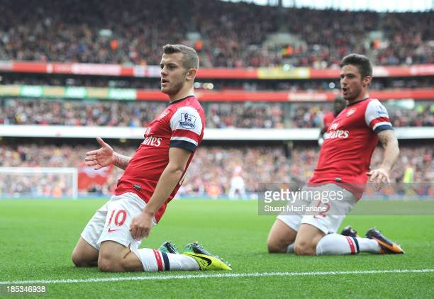 Jack Wilshere celebrates scoring his goal with Olivier Giroud during the match at Emirates Stadium on October 19 2013 in London England
