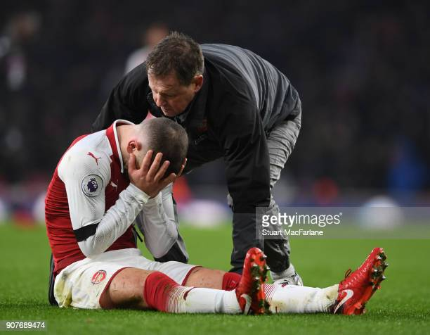 Jack Wilshere is treated by Arsenal physio Colin Lewin during the Premier League match between Arsenal and Crystal Palace at Emirates Stadium on...