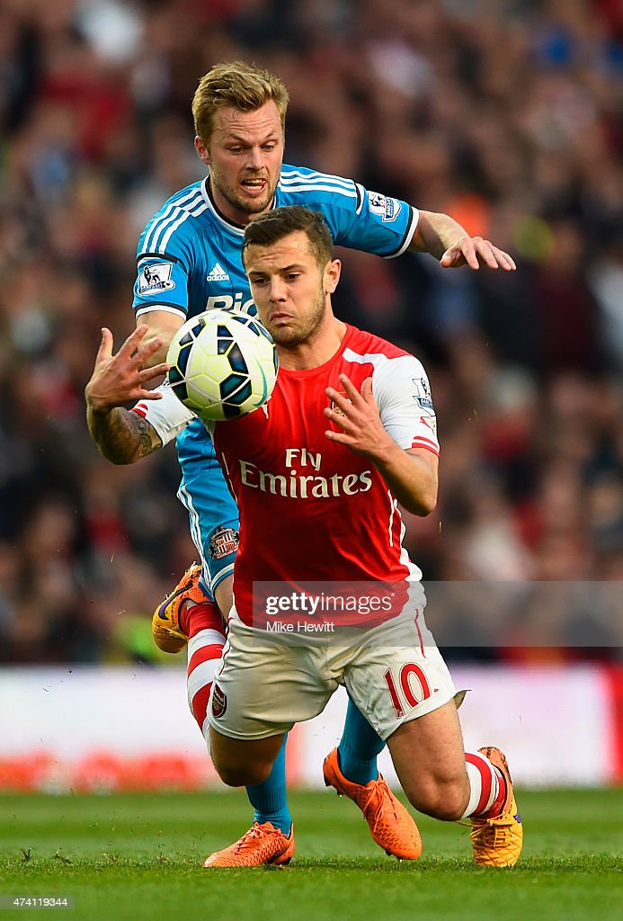 Jack Wilshere of Arsenal and Sebastian Larsson of Sunderland compete for the ball during the Barclays Premier League match between Arsenal and Sunderland at Emirates Stadium on May 20, 2015 in London, England.
