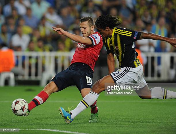 Jack Wilshere of Arsenal breaks past Bruno Alves of Fenerbahce during the UEFA Champions League Play Off first leg match between Fenerbache SK and...