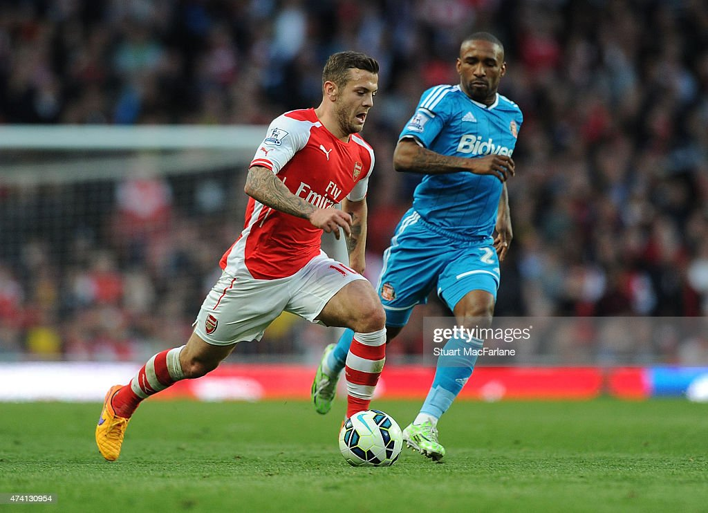 Jack Wilshere of Arsenal breaks past Jermain Defoe of Sunderland during the Barclays Premier League match between Arsenal and Sunderland at Emirates Stadium on May 20, 2015 in London, England.