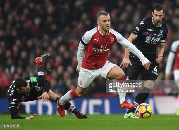 Jack Wilshere of Arsenal breaks past Luca Milivojevic and James McArthur of Crystal Palace during the Premier League match between Arsenal and...