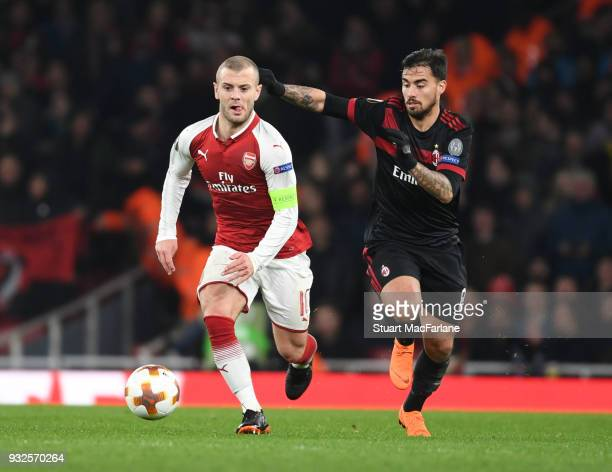 Jack Wilshere of Arsenal breaks past Suso of Milan during UEFA Europa League Round of 16 match between AC Milan and Arsenal at Emirates Stadium on...