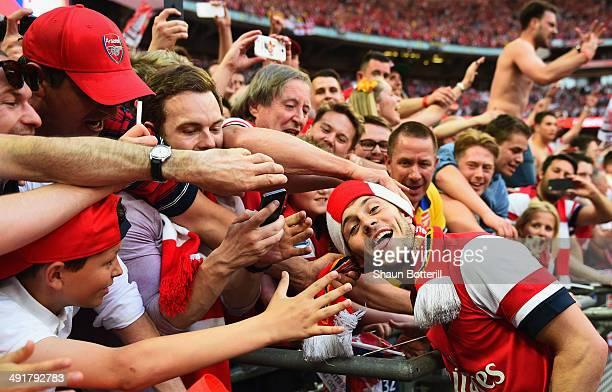 Jack Wilshere of Arsenal celebrates victory with fans after the FA Cup with Budweiser Final match between Arsenal and Hull City at Wembley Stadium on...