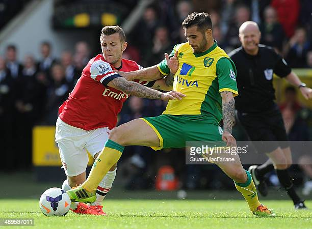 Jack Wilshere of Arsenal challenged by Bradley Johnson of Norwich during the Barclays Premier League match between Norwich City and Arsenal at Carrow...
