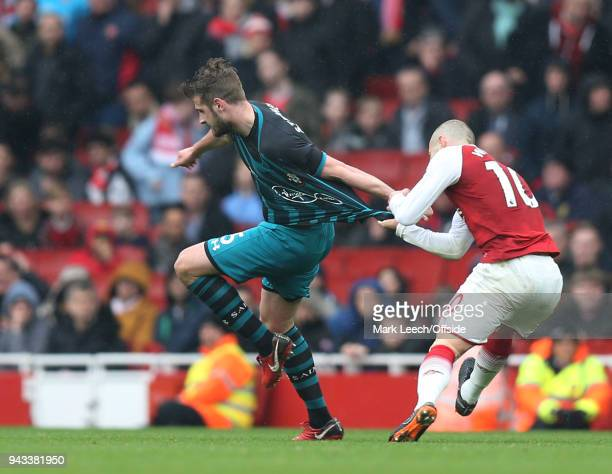 Jack Wilshere of Arsenal grabs the shirt of Jack Stephens of Southampton before the incident which saw a red card for Stephens during the Premier...