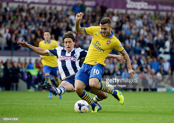 Jack Wilshere of Arsenal is challenged by Billy Jones of West Bromwich Albion during the Barclays Premier League match between West Bromwich Albion...