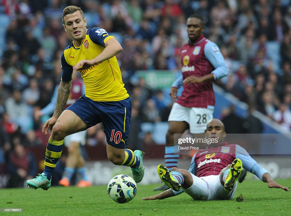 Jack Wilshere of Arsenal is challenged by Fabian Delph of Villa during the Barclays Premier League match between Aston Villa and Arsenal at Villa Park on September 20, 2014 in Birmingham, England.
