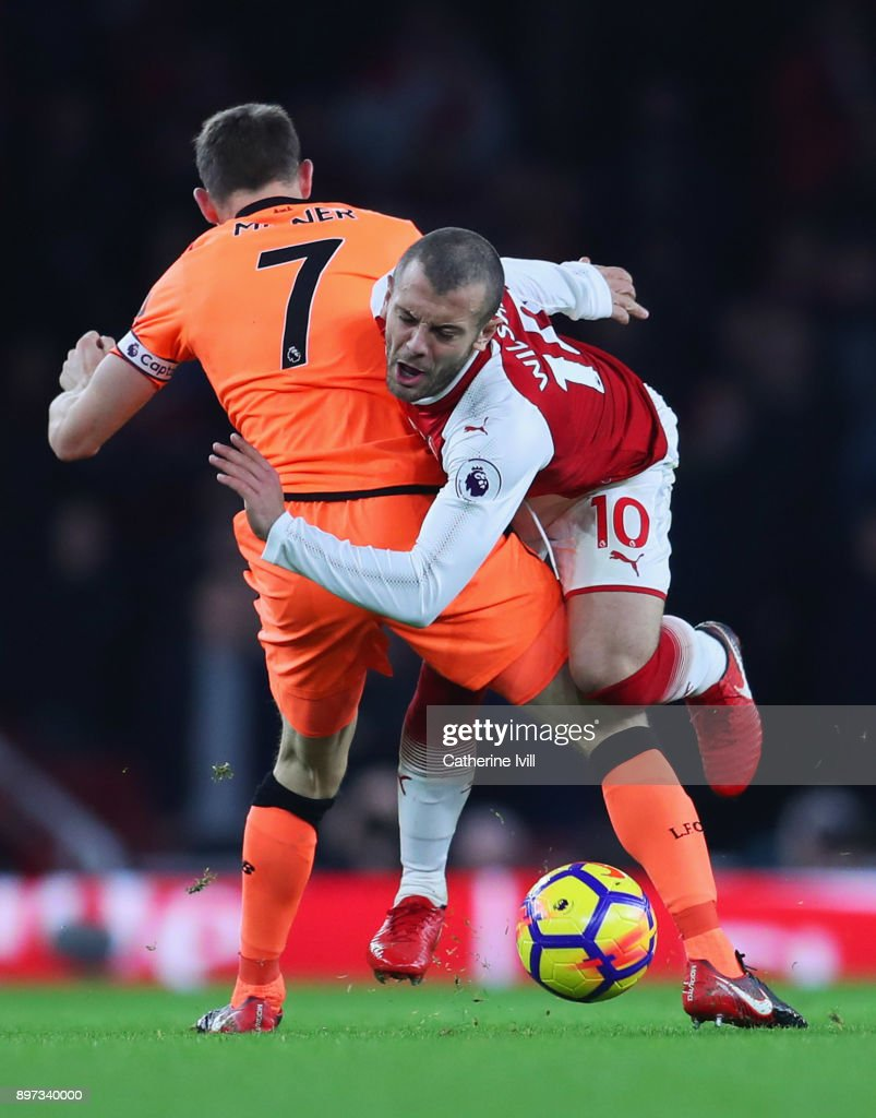 Jack Wilshere of Arsenal is challenged by James Milner of Liverpool during the Premier League match between Arsenal and Liverpool at Emirates Stadium on December 22, 2017 in London, England.