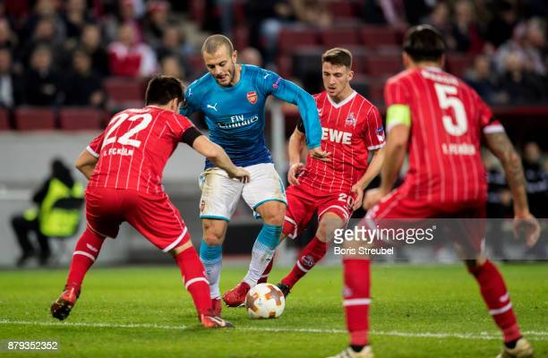 Jack Wilshere of Arsenal is challenged by players of 1FC Koeln during the UEFA Europa League group H match between 1 FC Koeln and Arsenal FC at...