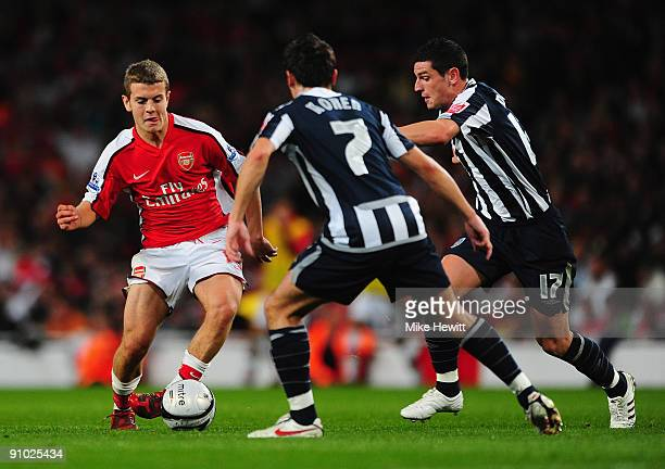 Jack Wilshere of Arsenal is challenged by Robert Koren and Graham Dorrans of West Bromwich Albion during the Carling Cup third round match between...