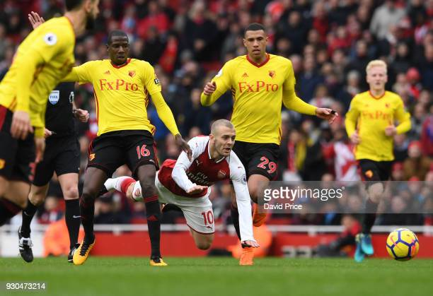 Jack Wilshere of Arsenal is fouled by Abdoulaye Doucoure and Etienne Capoue of Watford during the Premier League match between Arsenal and Watford at...