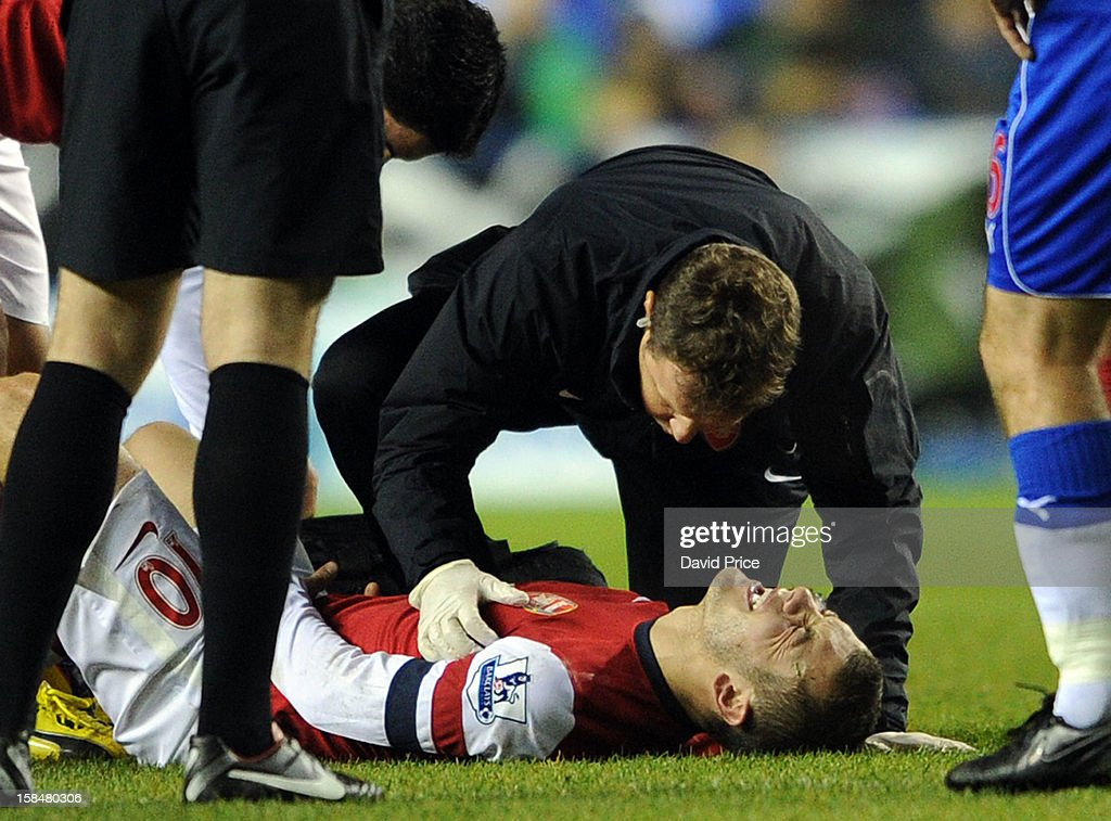 Jack Wilshere of Arsenal is treated for a injury by Arsenal Physio Colin Lewin during the Barclays Premier League match between Reading and Arsenal at Madejski Stadium on December 17, 2012 in Reading, England.