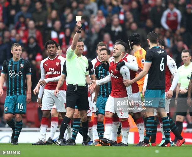 Jack Wilshere of Arsenal looks astonished as referee Andre Marriner shows him the yellow card during the Premier League match between Arsenal and...