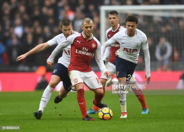 Jack Wilshere of Arsenal passes the ball under pressure from Eric Dier and Dele Alli of Tottenham during the Premier League match between Tottenham...