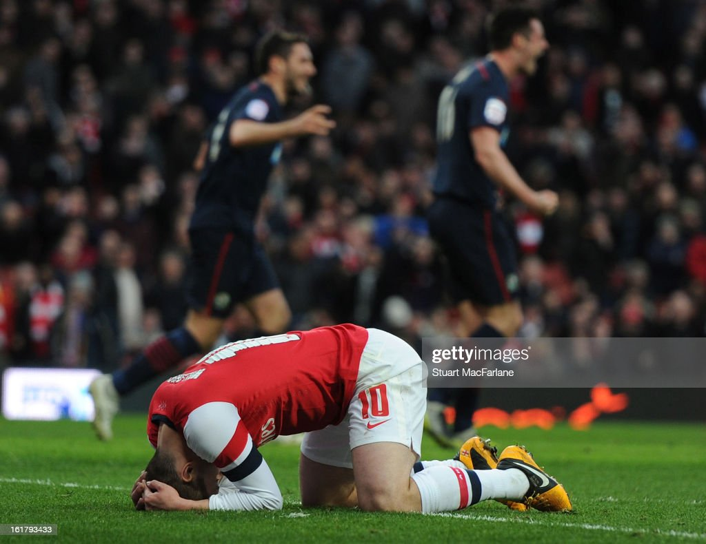 Jack Wilshere of Arsenal reacts as Blackburn players celebrate scoring the only goal of the game, during the FA Cup Fifth Round match between Arsenal and Blackburn Rovers at the Emirates Stadium on February 16, 2013 in London, England.