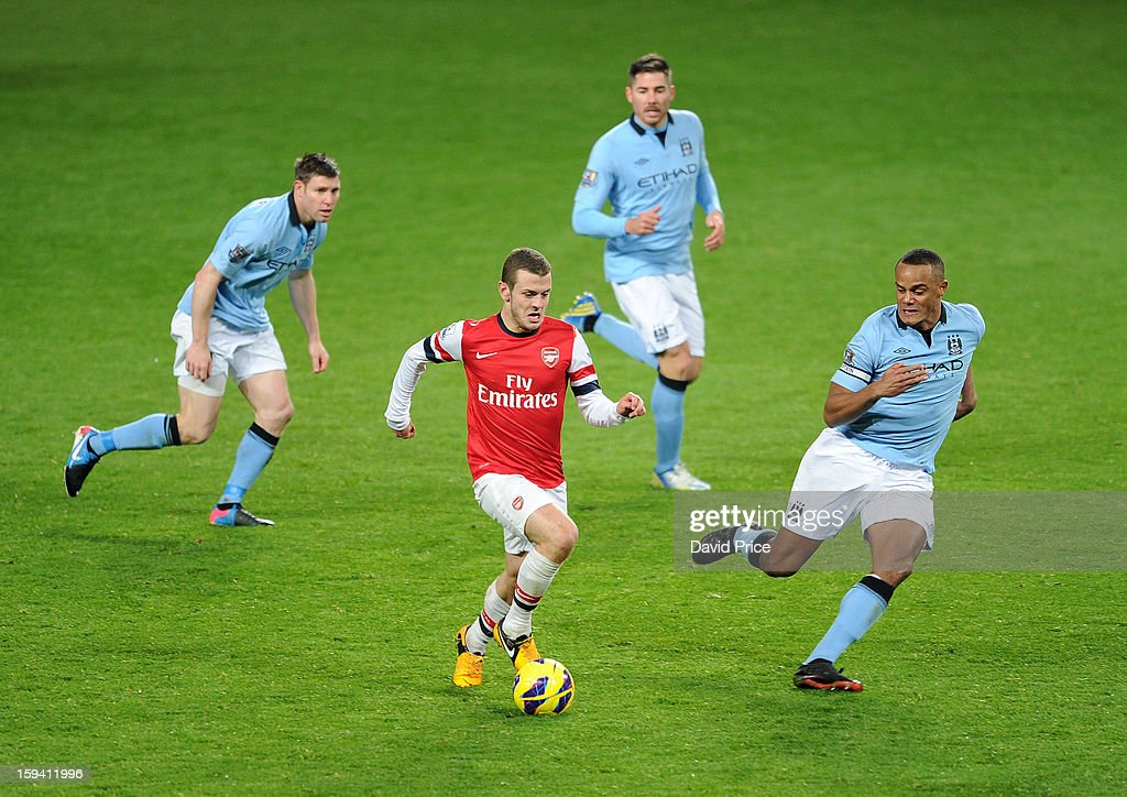 Jack Wilshere of Arsenal runs with the ball as (L-R) James Milner, Javi Garcia and Vincent Kompany of Man City close in during the Barclays Premier League match between Arsenal and Manchester City at Emirates Stadium on January 13, 2013 in London, England.