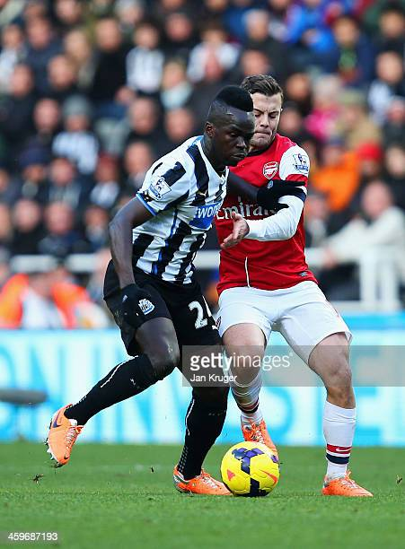 Jack Wilshere of Arsenal tackles Cheick Tiote of Newcastle United during the Barclays Premier League match between Newcastle United and Arsenal at St...