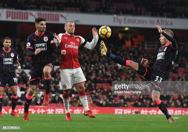 Jack Wilshere of Arsenal takes on Christopher Schindler and Florent Hadergjonaj of Huddersfield during the Premier League match between Arsenal and...