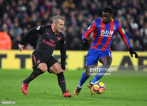 Jack Wilshere of Arsenal takes on Jeffrey Schlupp of Palace during the Premier League match between Crystal Palace and Arsenal at Selhurst Park on...