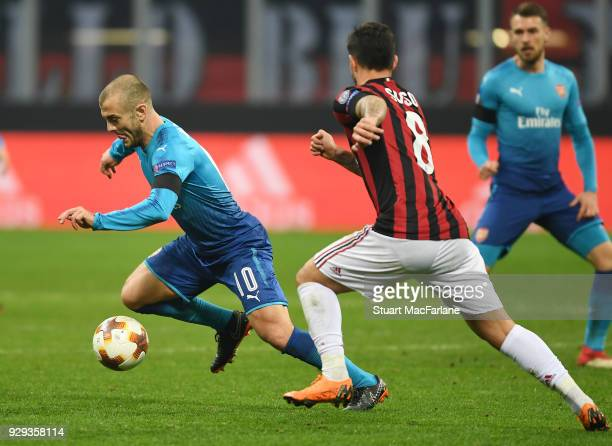 Jack Wilshere of Arsenal takes on Suso of Milan during UEFA Europa League Round of 16 match between AC Milan and Arsenal at the San Siro on March 8...