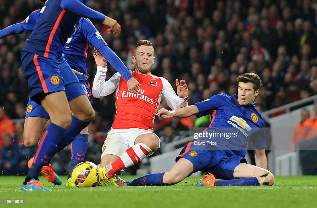 Jack Wilshere of Arsenal twists his ankle under a challenge from Paddy McNair of Manchester United during the match Arsenal v Manchester United in the Barcleys Premier League at Emirates Stadium on November 22, 2014 in London, England.