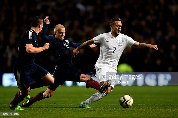 Jack Wilshere of England is challenged by Steven Naismith of Scotland and Scott Brown of Scotland during the International Friendly match between...