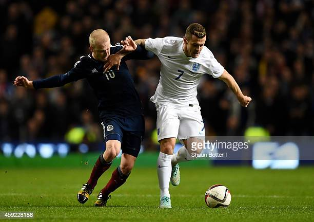 Jack Wilshere of England is challenged by Steven Naismith of Scotland during the International Friendly match between Scotland and England at Celtic...