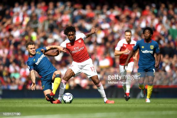 Jack Wilshere of West Ham United battles for posession with Alex Iwobi of Arsenal during the Premier League match between Arsenal FC and West Ham...