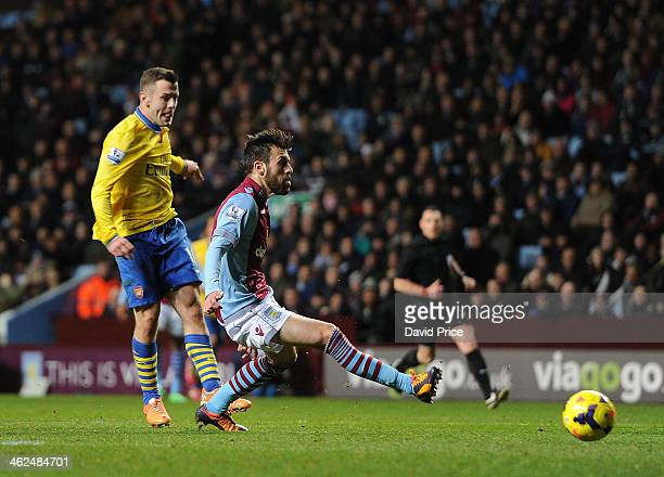 Jack Wilshere scores Arsenal's 1st goal past Antonio Luna of Villa during the Barclays Premier League match between Aston Villa and Arsenal at Villa...