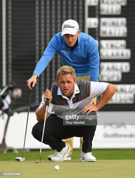 Jack Winer of Abridge Golf Country Club and James Watts of Kingsway Golf Centre line up a putt on the second play off hole on the 18th green during...