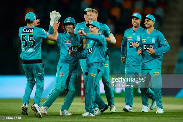 Jack Wood of the Heat celebrates with team mates after taking the wicket of Ben Dunk of the Stars during the Big Bash League match between the...