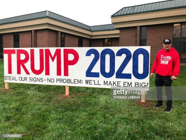 Jack Worthington poses in front of one of his homemade Trump signs in Newtown, Pennsylvania on October 28, 2020. - The millions of signs that...