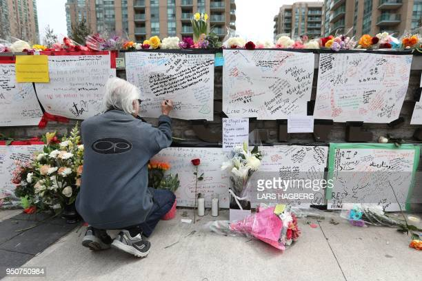 TOPSHOT Jack Young leaves a notes on April 24 at a makeshift memorial for victims in the van attack in Toronto Ontario A van driver who ran over 10...