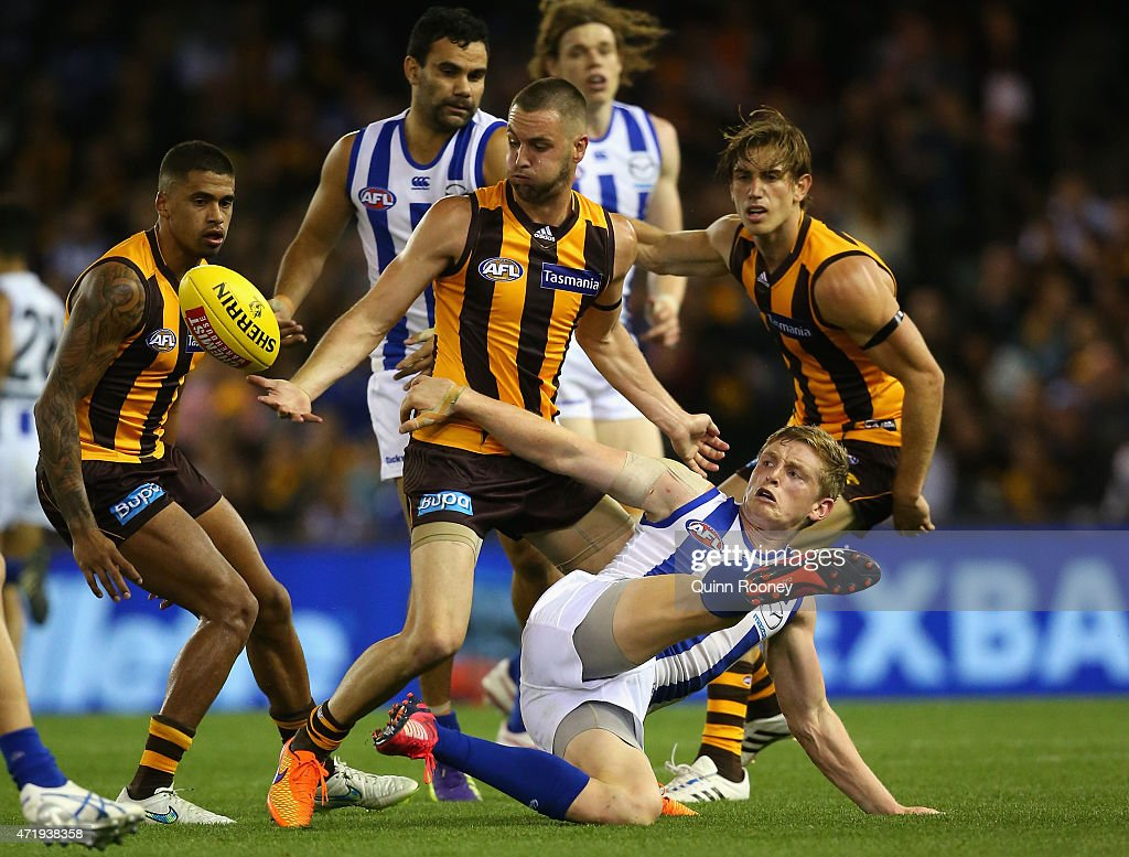 Jack Ziebell of the Kangaroos attempts to kick whilst being tackled by Matt Suckling of the Hawks during the round five AFL match between the North Melbourne Kangaroos and the Hawthorn Hawks at Etihad Stadium on May 2, 2015 in Melbourne, Australia.