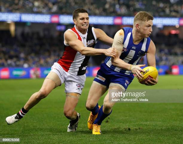 Jack Ziebell of the Kangaroos is tackled by Leigh Montagna of the Saints during the 2017 AFL round 13 match between the North Melbourne Kangaroos and...