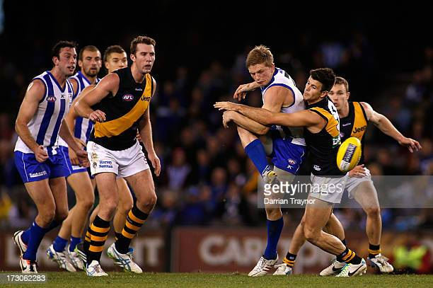 Jack Ziebell of the Kangaroos kicks the ball as Trent Cotchin during the round 15 AFL match between the North Melbourne Kangaroos and the Richmond...