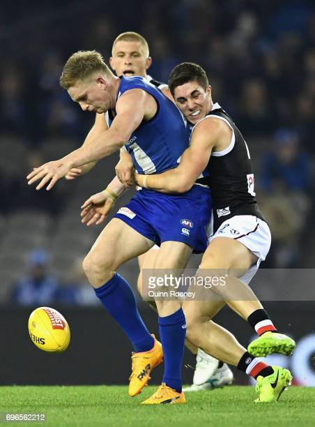 Jack Ziebell of the Kangaroos kicks whilst being tackled by Jade Gresham of the Saints during the round 13 AFL match between the North Melbourne...