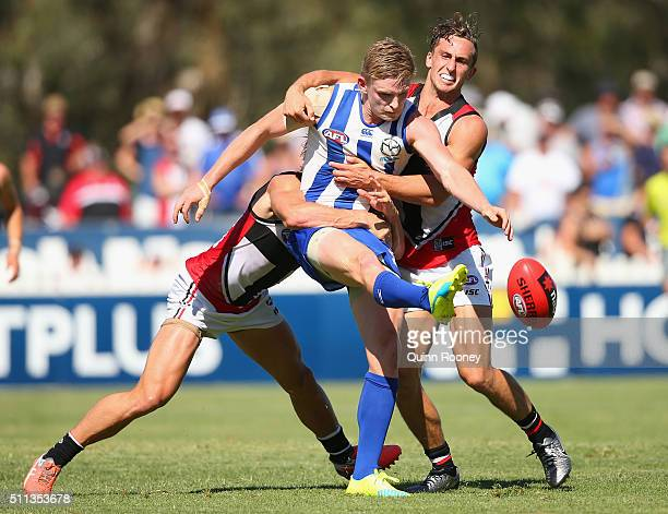 Jack Ziebell of the Kangaroos kicks whilst being tackled by Maverick Weller and Luke Dunstan of the Saints during the 2016 AFL NAB Challenge match...