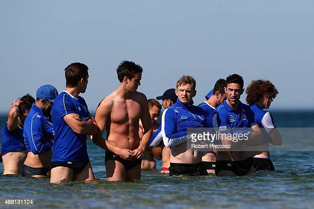 Jack Ziebell walks through water with teammates during a North Melbourne Kangaroos AFL recovery session on September 14 2015 in Melbourne Australia