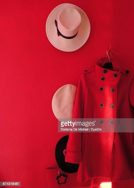Jacket And Headwear Hanging On Red Wall