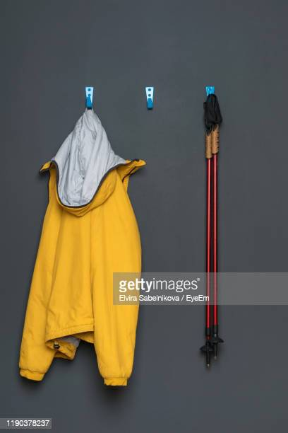 jacket and hiking poles hanging on gray wall - yellow coat stock pictures, royalty-free photos & images
