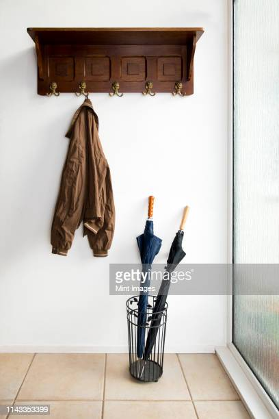 jacket and umbrellas in foyer of home - 収納ラック ストックフォトと画像