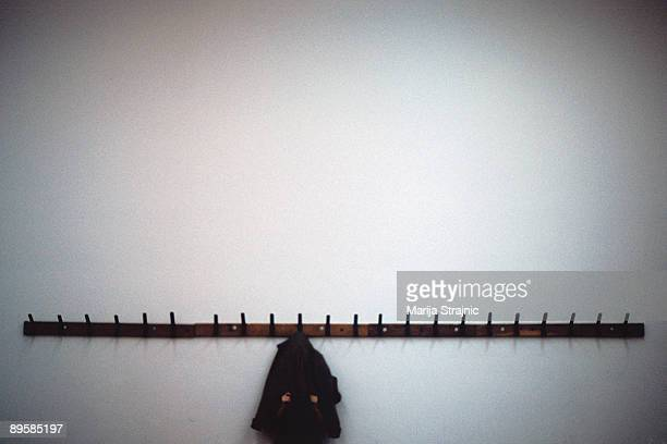 jacket hanging from coat hooks on a white wall - marija mauer stock-fotos und bilder