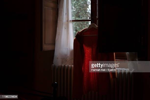 jacket hanging on coathanger against window at home - san miniato stock pictures, royalty-free photos & images