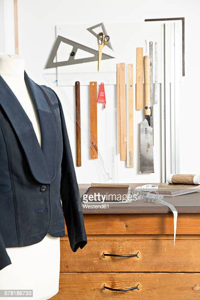 Jacket on dressmakers model and tools in manufacturers workshop